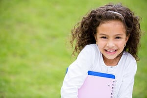 Happy schoolgirl outdoors carrying notebooks and smiling